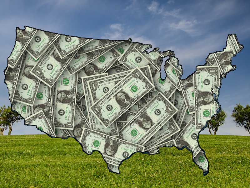 US map filled with bank notes to illustrate buying vacant land - against a green field